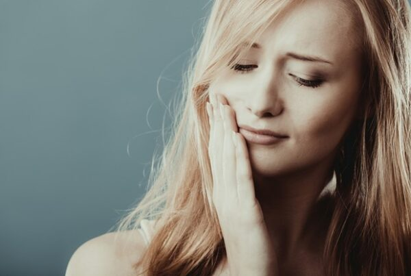 close up of woman with blonde hair touching face because of toothache