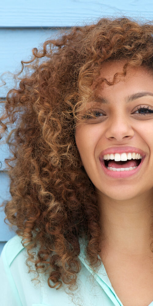 Cheerful young woman with curly hair smiling